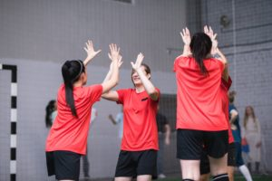 Team of active girls in sports uniform expressing triumph by high-five gesture